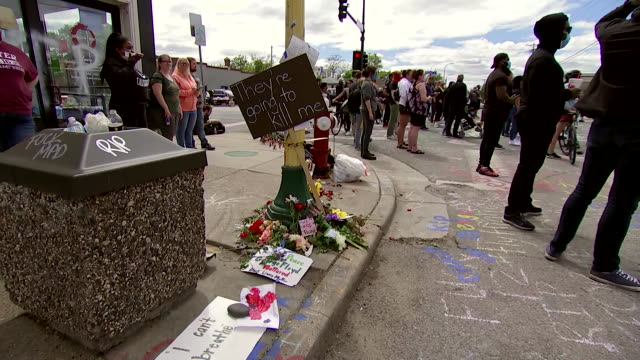 establishing shot of signs and flowers left at the location where george floyd was killed in minneapolis, minnesota. - minnesota stock videos & royalty-free footage