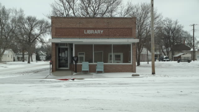 Establishing shot of small town library on a snow-covered main street during winter.