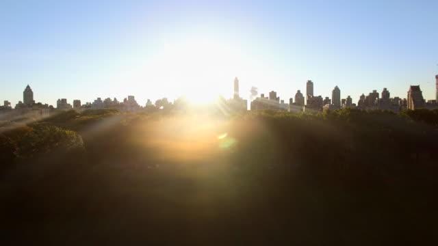 vidéos et rushes de establishing shot of sunrise and city silhouette. night to day transition - inclinaison vers le haut