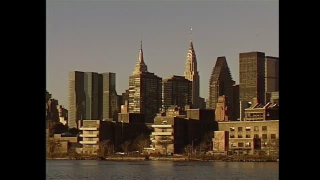 establishing shot of the 59th street bridge and zoom in to the new york city skyline in the 1990s - クイーンズボロ橋点の映像素材/bロール