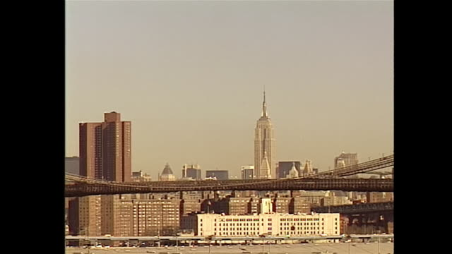 vídeos y material grabado en eventos de stock de establishing shot of the brooklyn promenade looking toward the brooklyn bridge and empire state building in new york city during the 1990s. - music or celebrities or fashion or film industry or film premiere or youth culture or novelty item or vacations