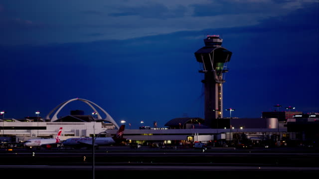 establishing shot of the control tower and theme building, los angeles international airport, late evening. - air traffic control tower stock videos & royalty-free footage
