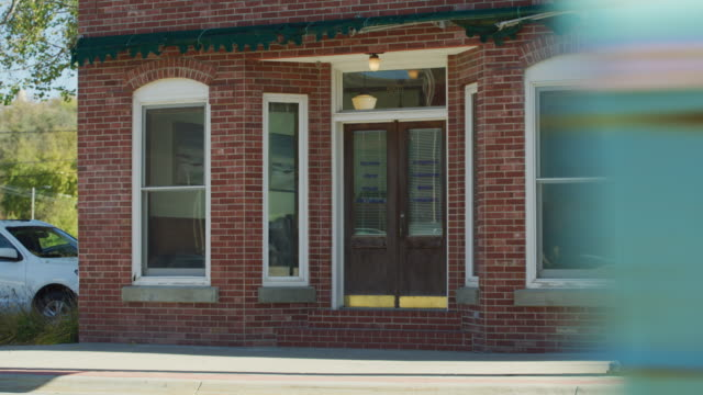 establishing shot of the exterior brick facade of an old building on main street in small town america; a vintage pick up eclipses frame. - establishing shot stock videos & royalty-free footage
