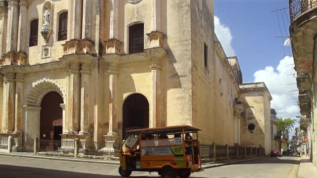 establishing shot of the iglesia de las mercedes where a 'motoneta' passes by on april 15 in old havana, havana, cuba. - temple building stock videos & royalty-free footage