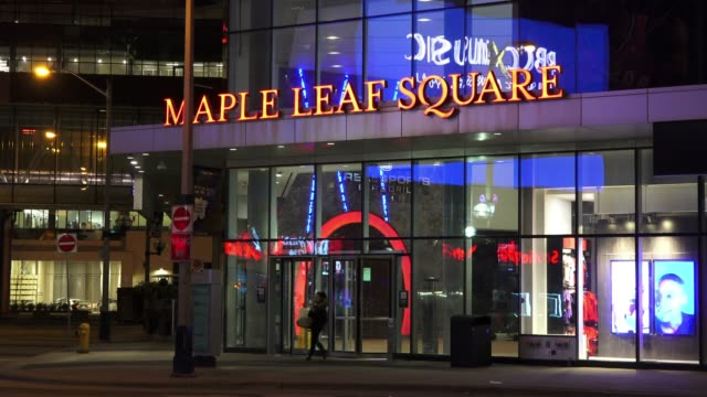 Establishing shot of the Maple Leaf Square at night The sign of the place is illuminated in orange color There are many reflections in the glass...