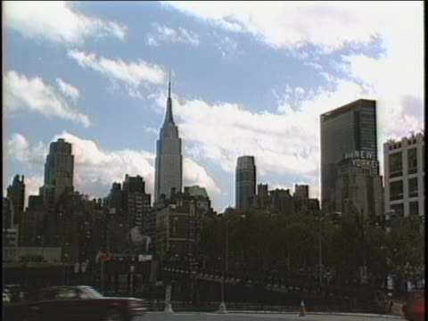 establishing shot of the new york city skline with traffic passing by from the west side. - skyline stock videos & royalty-free footage