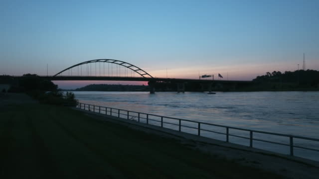 establishing shot of the sunrise behind a bridge over the missouri river in sioux city iowa - aerial or drone pov or scenics or nature or cityscape stock videos & royalty-free footage