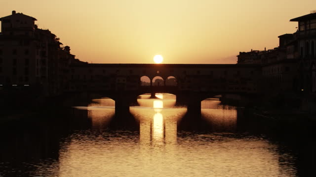 establishing shot of the sunset over ponte vecchio and the arno river in florence, italy. - ponte点の映像素材/bロール