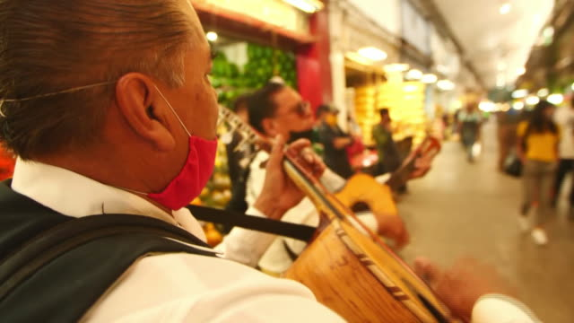 establishing shot of three men playing intruments at mexico city food market during the coronavirus pandemic. - healthcare and medicine or illness or food and drink or fitness or exercise or wellbeing stock videos & royalty-free footage