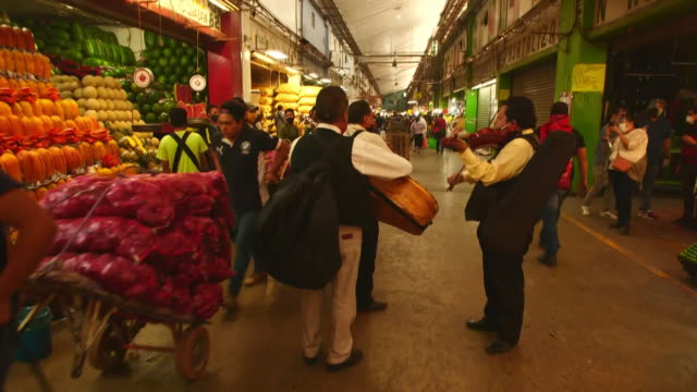 establishing shot of three men playing intruments at mexico city food market during the coronavirus pandemic - healthcare and medicine or illness or food and drink or fitness or exercise or wellbeing stock videos & royalty-free footage