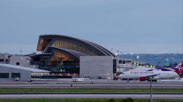 Establishing shot of Tom Bradley International Terminal, Los Angeles International Airport, with a Virgin America Airbus A320 taxiing past, late afternoon.