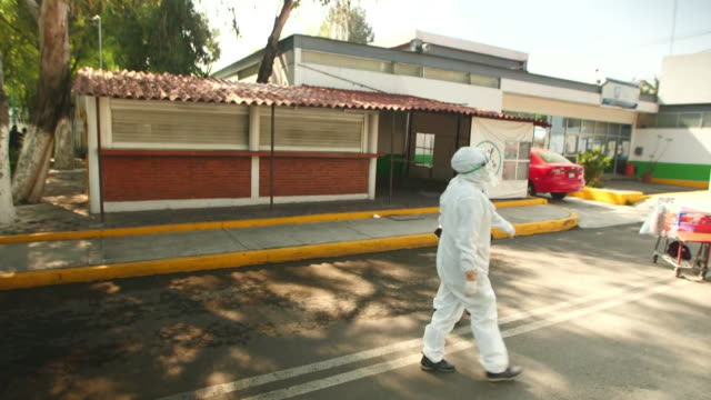 establishing shot of two people in full ppe walking into a mexico city food market during the coronavirus pandemic. - healthcare and medicine or illness or food and drink or fitness or exercise or wellbeing 個影片檔及 b 捲影像