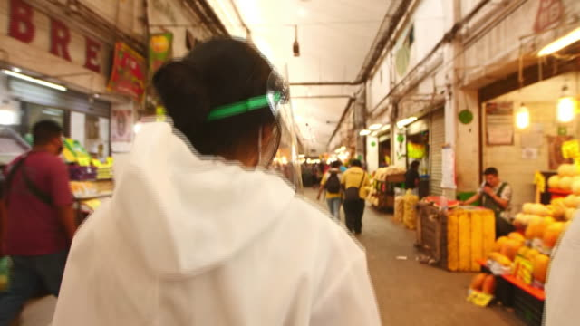 establishing shot of two people in full ppe walking through mexico city food market during the coronavirus pandemic - healthcare and medicine or illness or food and drink or fitness or exercise or wellbeing stock videos & royalty-free footage