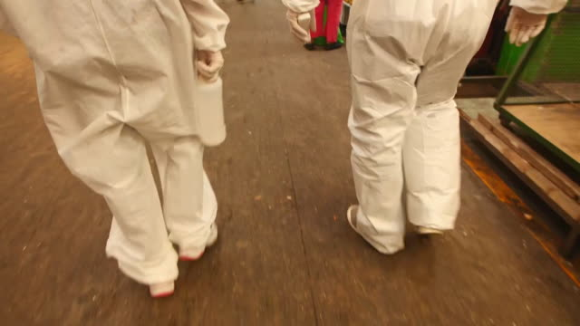 establishing shot of two people's legs in full ppe walking through mexico city food market during the coronavirus pandemic. - healthcare and medicine or illness or food and drink or fitness or exercise or wellbeing stock videos & royalty-free footage