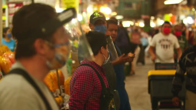 establishing shot of vendors in face shields at mexico city food market during the coronavirus pandemic. - healthcare and medicine or illness or food and drink or fitness or exercise or wellbeing 個影片檔及 b 捲影像