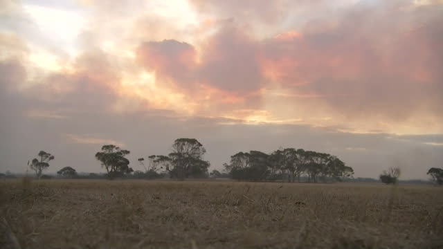 establishing shot on kangaroo island at sunset. smoke from nearby fires is visible in the sky. - environment or natural disaster or climate change or earthquake or hurricane or extreme weather or oil spill or volcano or tornado or flooding stock videos & royalty-free footage