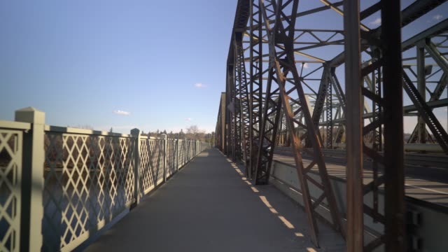 vídeos de stock e filmes b-roll de establishing shot on pedestrian path by bridge - perspetiva diminutiva