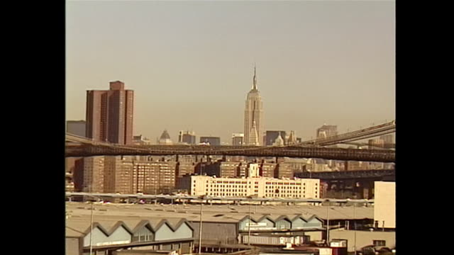 establishing shot panning the new york city skyline and warehouses in brooklyn toward the brooklyn bridge and empire state building in the 1990s - music or celebrities or fashion or film industry or film premiere or youth culture or novelty item or vacations stock-videos und b-roll-filmmaterial