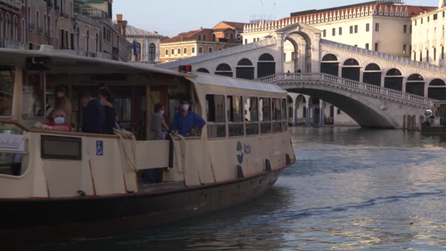 establishing shot passing a boat on the grand canal in venice italy during the coronavirus pandemic passengers on board are wearing masks over their... - healthcare and medicine or illness or food and drink or fitness or exercise or wellbeing video stock e b–roll