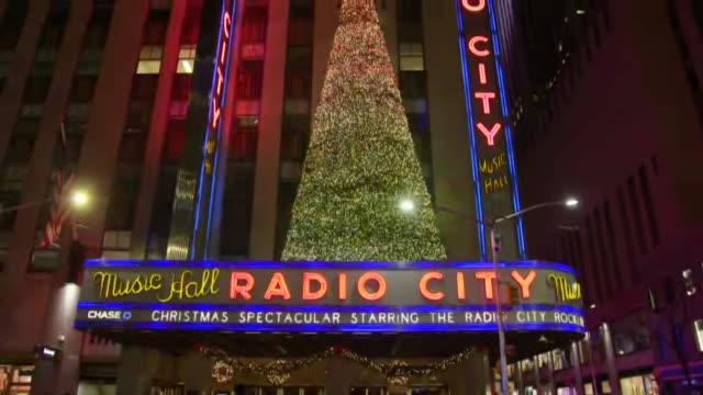 establishing shot slow tilt up of radio city music hall holiday exterior. - radio city music hall stock-videos und b-roll-filmmaterial