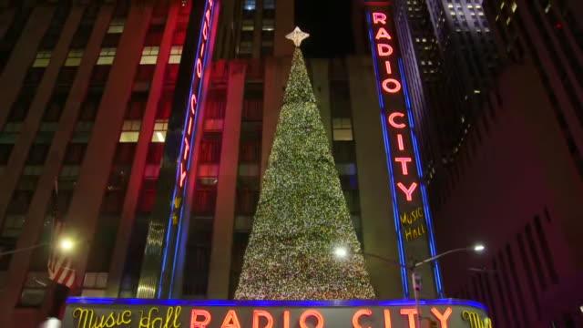 establishing shot tilt up of radio city music hall holiday exterior. - radio city music hall stock-videos und b-roll-filmmaterial