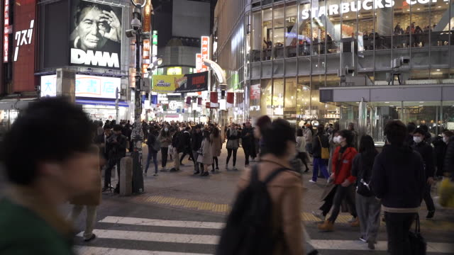 establishing shot walking through a crowded shibuya crosswalk in tokyo, japan. most people are wearing face masks amid coronovirus fears. - healthcare and medicine or illness or food and drink or fitness or exercise or wellbeing点の映像素材/bロール