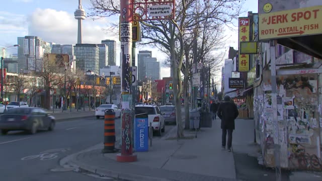 establishing shot zooming out from kensington market sign to street corner with toronto skyline and cn tower in the background. - music or celebrities or fashion or film industry or film premiere or youth culture or novelty item or vacations stock videos & royalty-free footage