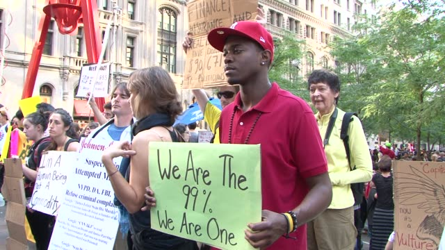 establishing shots of occupy wall. st. protest / zuccotti park / liberty square / focus on signs, placards, t-shirts occupy wall street protests on... - occupy protests stock videos & royalty-free footage