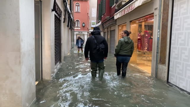 vídeos y material grabado en eventos de stock de establishing shots of tourists walking through flood waters in venice, italy. - environment or natural disaster or climate change or earthquake or hurricane or extreme weather or oil spill or volcano or tornado or flooding