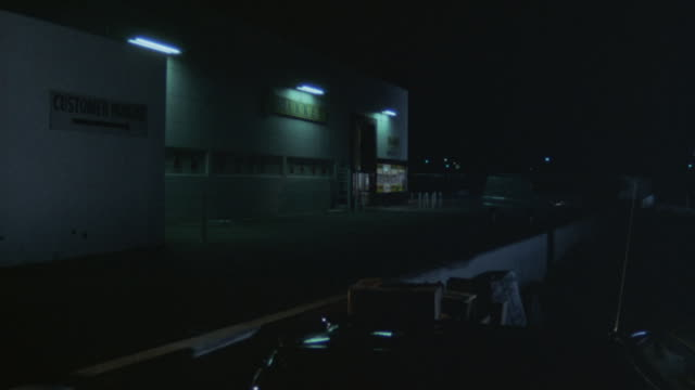 Establishing-shot of an industrial warehouse at night with a sign on one wall that says, Customer Parking.