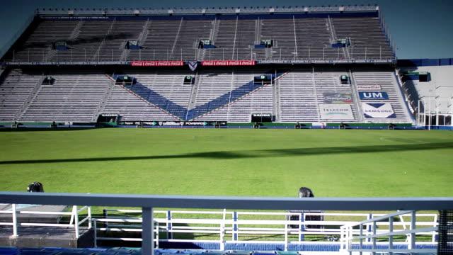 vídeos y material grabado en eventos de stock de estadio jose amalfitani soccer stadium, grass field, pitch, empty grandstand, bleachers, railing fg, dolly right. - barra futbol