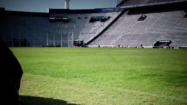 vídeos y material grabado en eventos de stock de estadio jose amalfitani soccer stadium grass field pitch empty grandstand bleachers black tarps covering upright objects fg unidentifiable person... - campo de fútbol