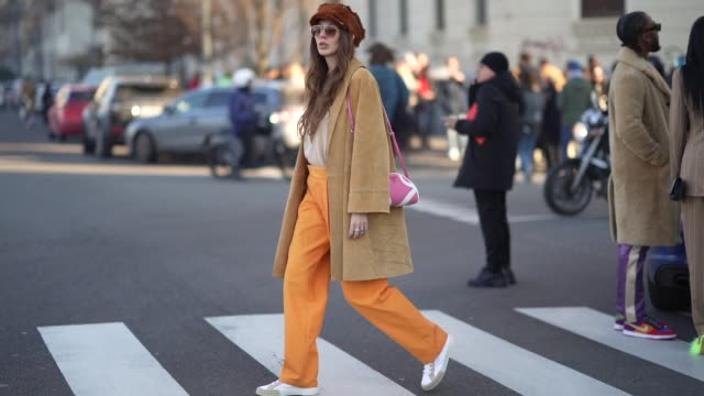 vidéos et rushes de estelle chemouny wears a brown beret hat, aviator sunglasses, a beige suede coat, a pink prada bag, orange pants, prada sneakers shoes, outside msgm,... - casquette
