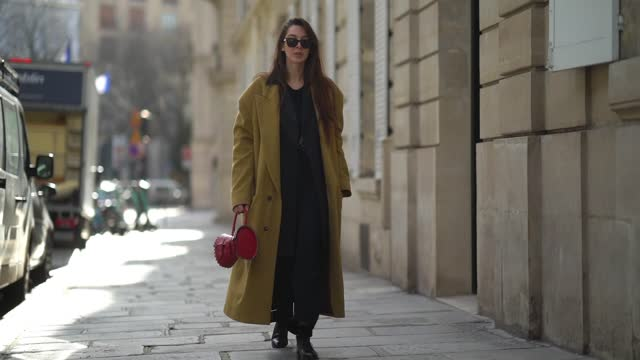 estelle chemouny wears ray ban sunglasses, a brown / khaki wool oversized long coat, a red alaia leather bag, a black top, a dark gray oversized... - gray jacket stock videos & royalty-free footage