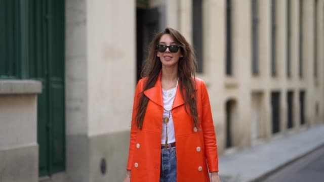 estelle chemouny wears ray ban sunglasses, an orange leather long coat from prada, a white t-shirt, a necklace, a colorful scarf as a belt, blue... - street style点の映像素材/bロール