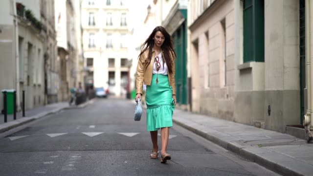 estelle chemouny wears red sunglasses, a brown/beige leather jacket from miu miu, a white t-shirt, a green ruffled and pleated leather skirt from miu... - street style点の映像素材/bロール