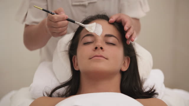vídeos de stock e filmes b-roll de  ds esthetician applying facial mask to client / stowe, vermont, united states - cuidado com o corpo