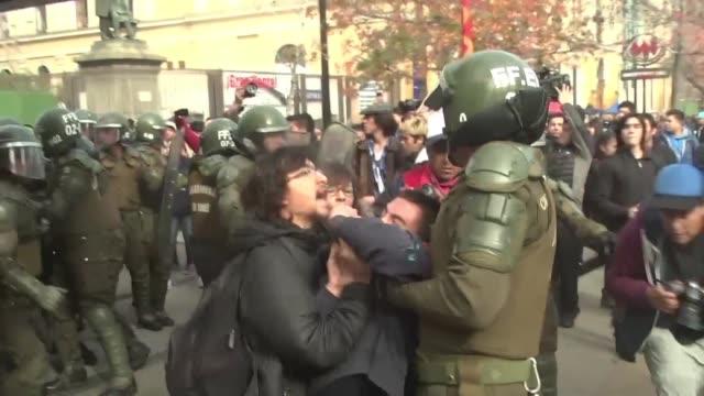 vídeos de stock e filmes b-roll de estudiantes chilenos se enfrentaron con la policia el miercoles en santiago durante una marcha para exigir al gobierno que acelere la implantacion de... - exigir