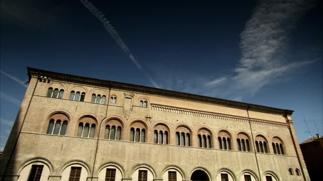 ethereal jet trails contrast with the solid architecture of the bishop's palace of parma, italy. available in hd. - parmigiano video stock e b–roll
