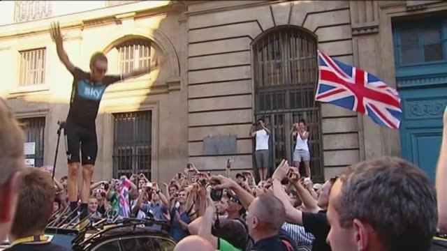 chris froome defends team sky; t22071214 / tx france: paris: ext bradley wiggins jumping up onto car to acknowledge the cheers and applause of fans... - tour de france stock videos & royalty-free footage