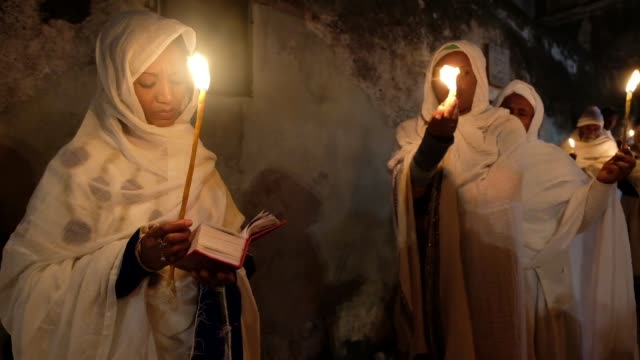 ethiopian orthodox christians light candles during the holy fire ceremony at deir elsultan monastery located on roof of the church of holy sepulchre... - 式典点の映像素材/bロール