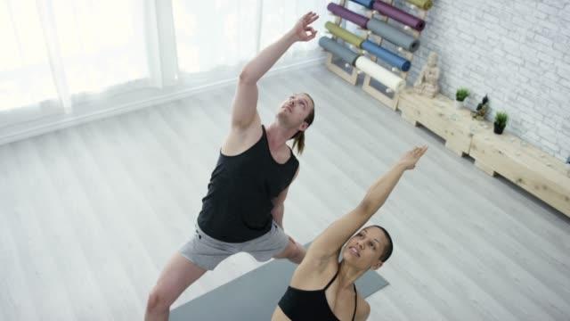ethnisches erwachsenes ehepaar beim yoga gemeinsam im fitnessstudio - yogastudio stock-videos und b-roll-filmmaterial