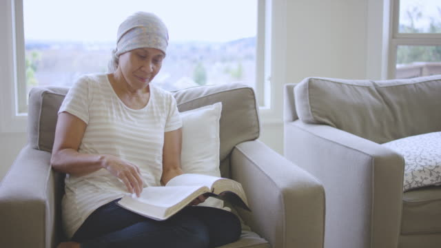 Ethnic adult female cancer patient reading the bible