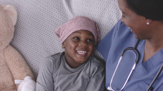 ethnic boy with cancer smiling at his nurse - patient stock videos & royalty-free footage