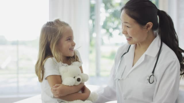 Ethnic Doctor Comforting Girl with Teddy Bear