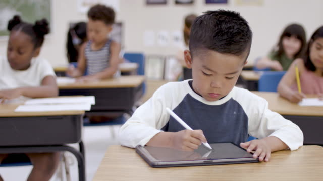 ethnic elementary student working on a digital tablet in a classroom - fatcamera stock videos and b-roll footage