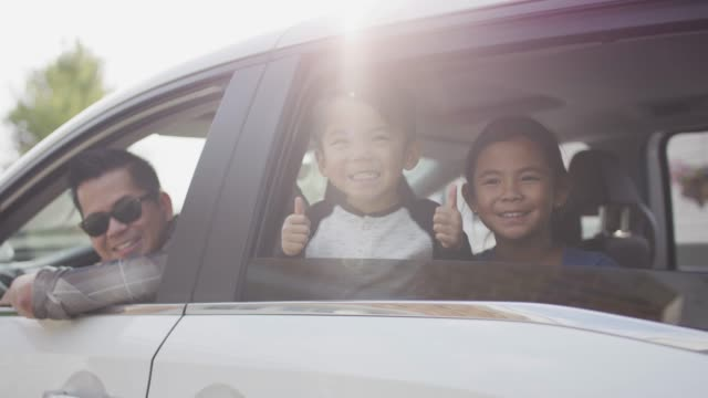 ethnic family looking out car windows - innocenza video stock e b–roll