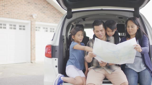 ethnic family sitting in back of car and looking at a map - vehicle seat stock videos & royalty-free footage