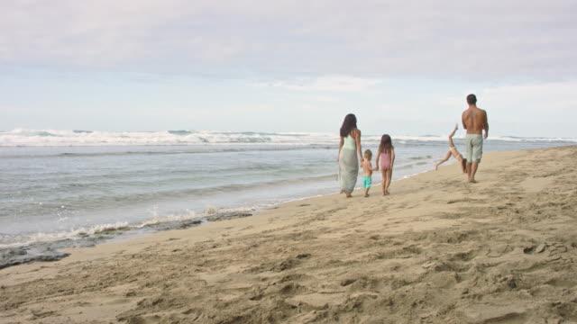 Ethnic family walking along beach