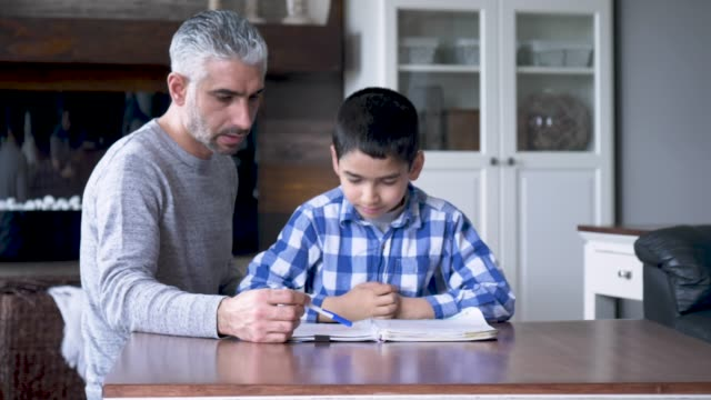 ethnic father helping his son with homework - elementary age stock videos & royalty-free footage